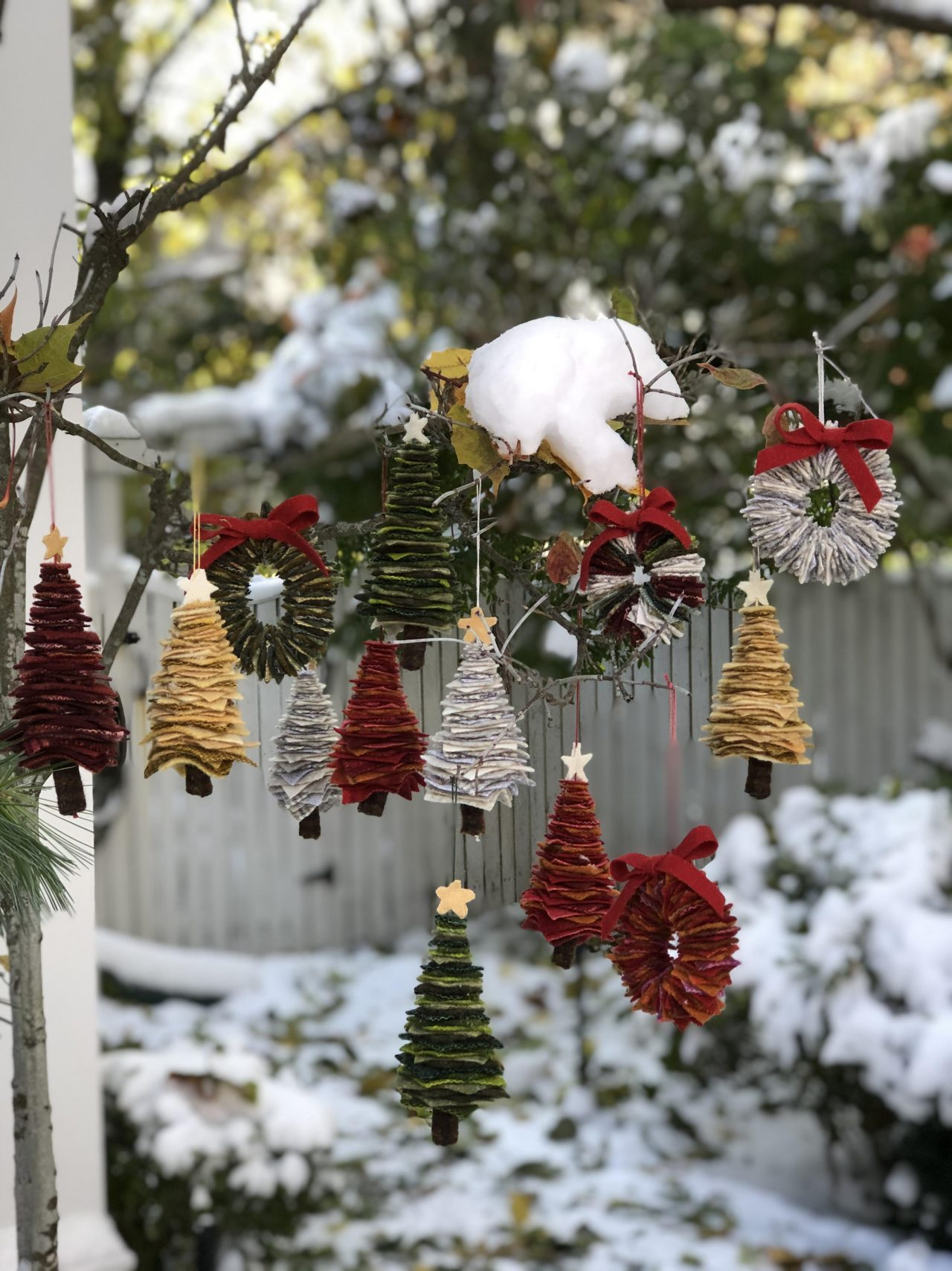 Mini textile christmas tree decorations hanging on a snowy tree by Yvonne Iten-Scott