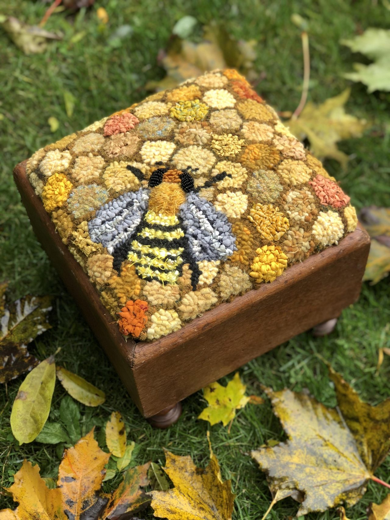 A textile art footstool cover featuring honeycomb background and a bee by Yvonne Iten-Scott
