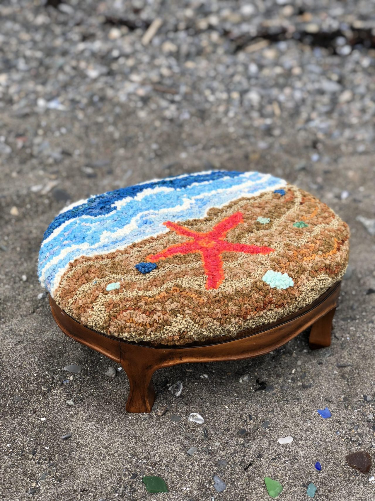 A wooden footstool with a hooked art image of a beach and red starfish by Yvonne Iten-Scott