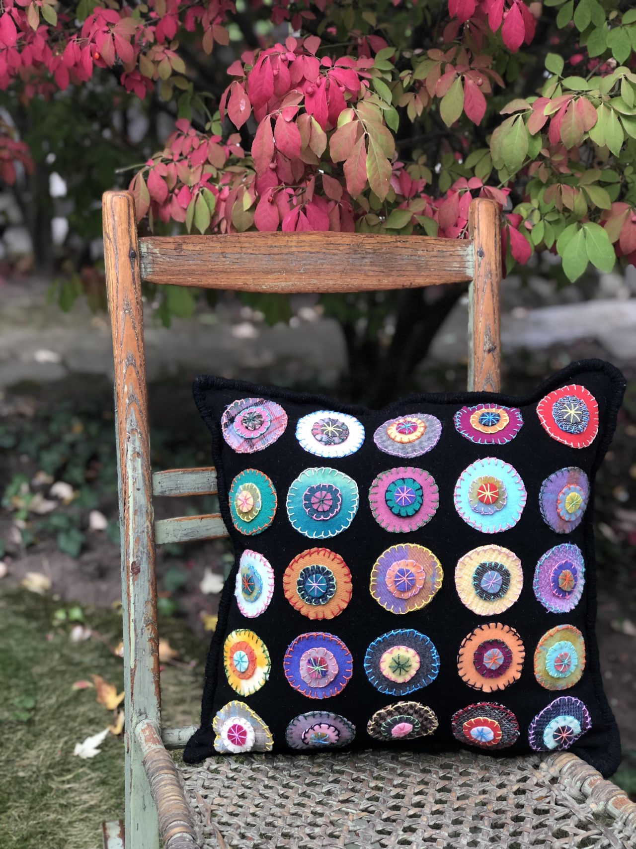 A black cushion with colourful circle pieces of fabric stitched onto it by Yvonne Iten-Scott.