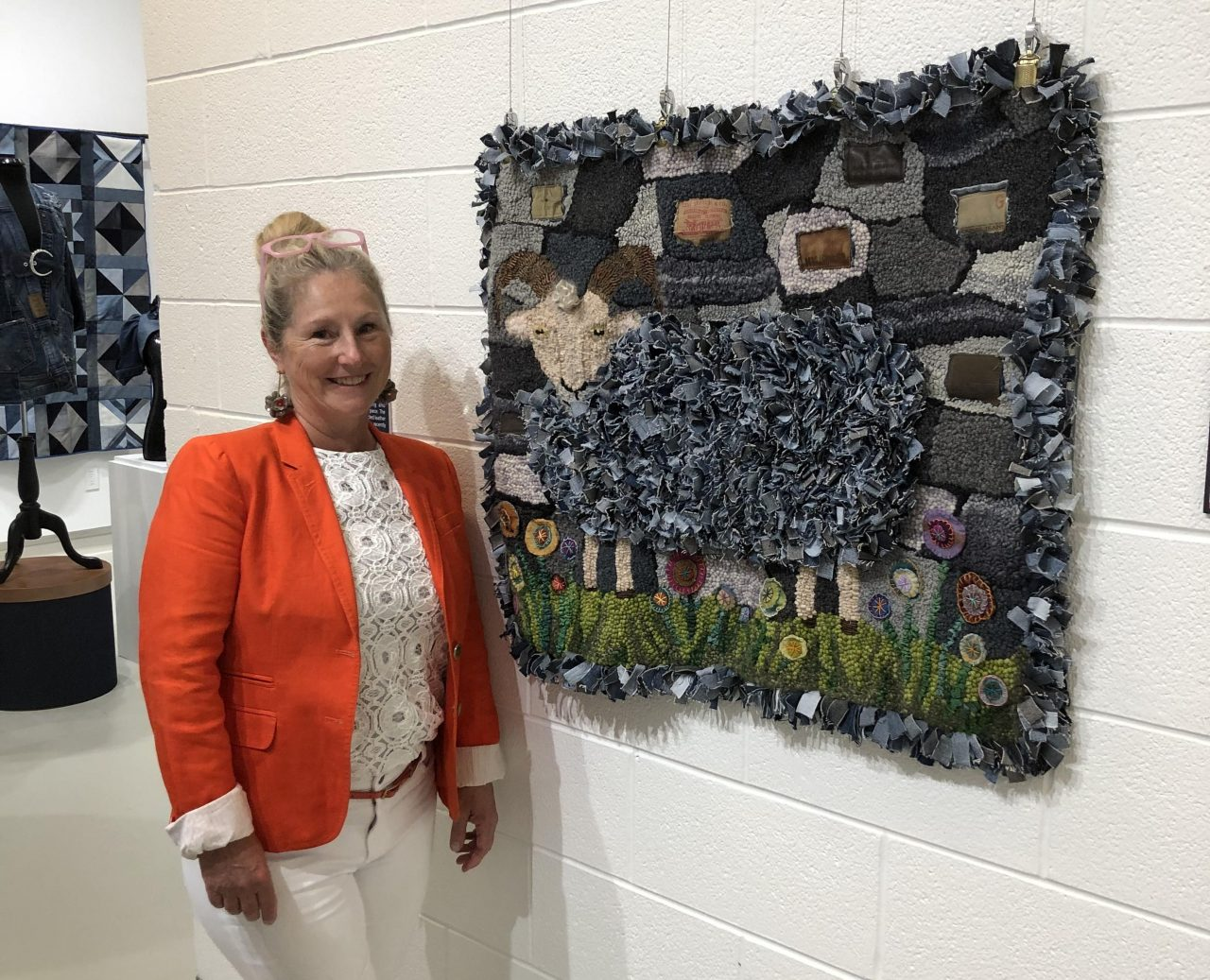 Artist Yvonne Iten-Scott standing by her textile art of a sheep made from denim scraps in a white gallery