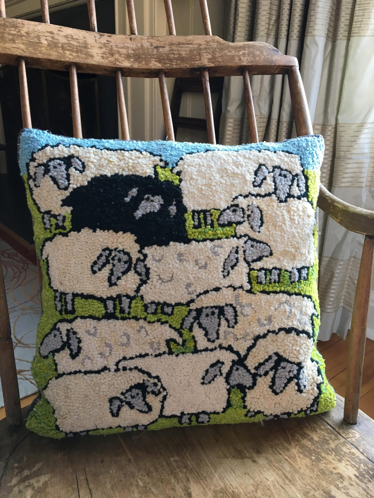 A hooked cushion with 10 white sheep and one black sheep on a wooden chair by Yvonne Iten-Scott.