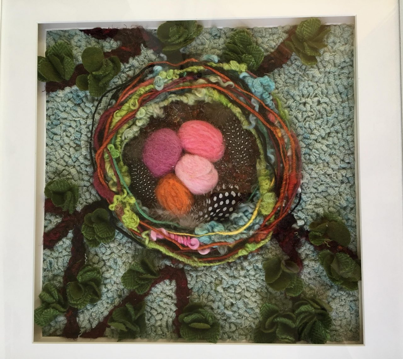 A hooked piece of textile art featuring a colourful birds nest on a green background by Yvonne Iten-Scott.
