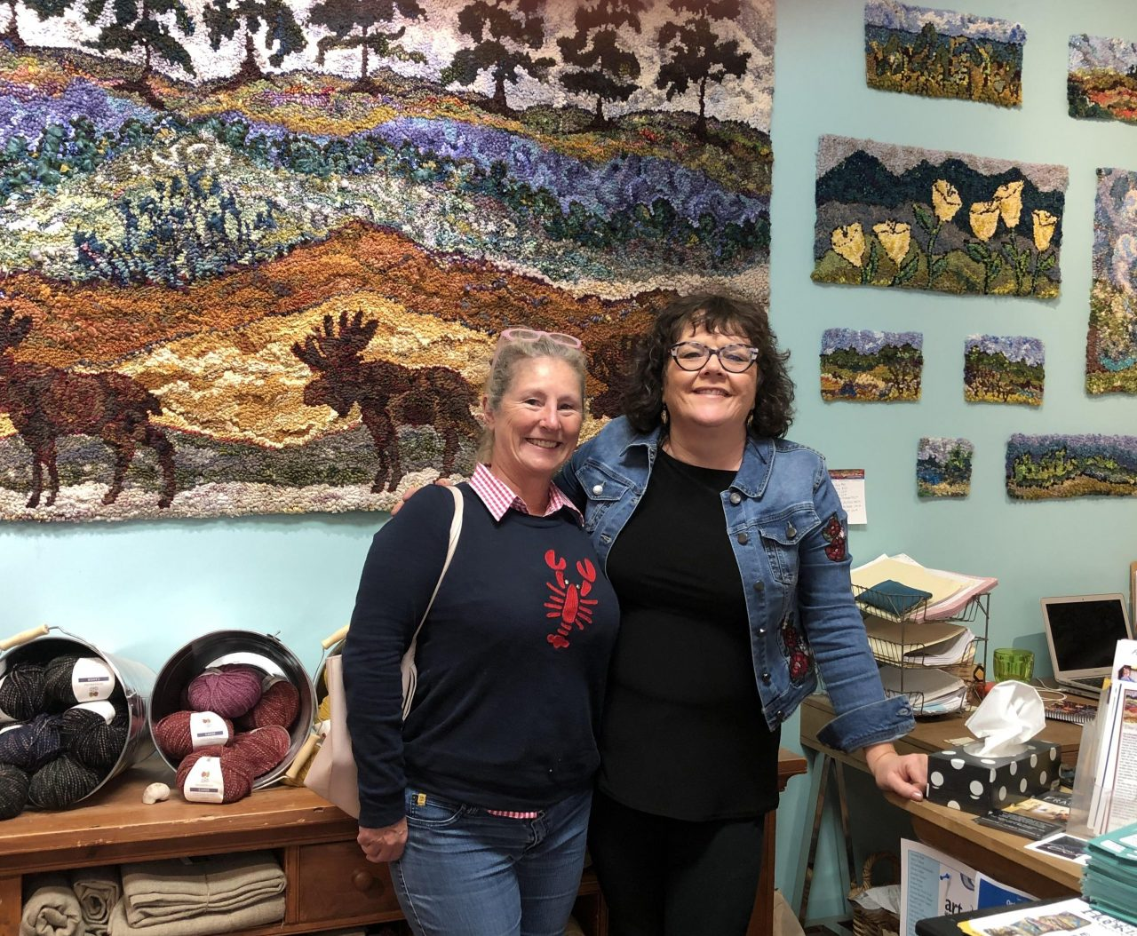 Yvonne Iten-Scott with Deanne Fitzpatrick standing in front of a wall of hooked art in Deanne's studio.