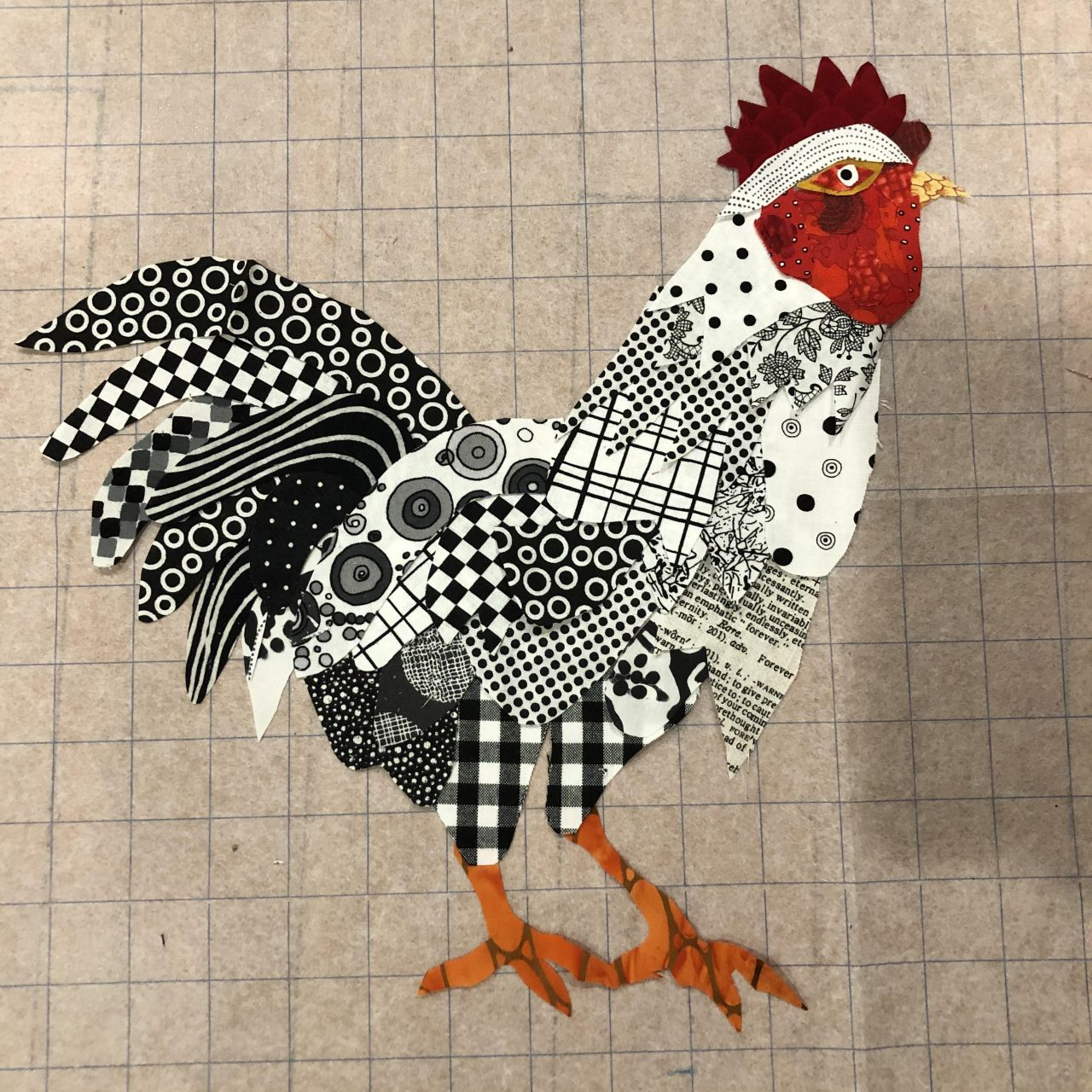An applique cockerel with a black and white patterned body, orange feet and a red face by Yvonne Iten-Scott.