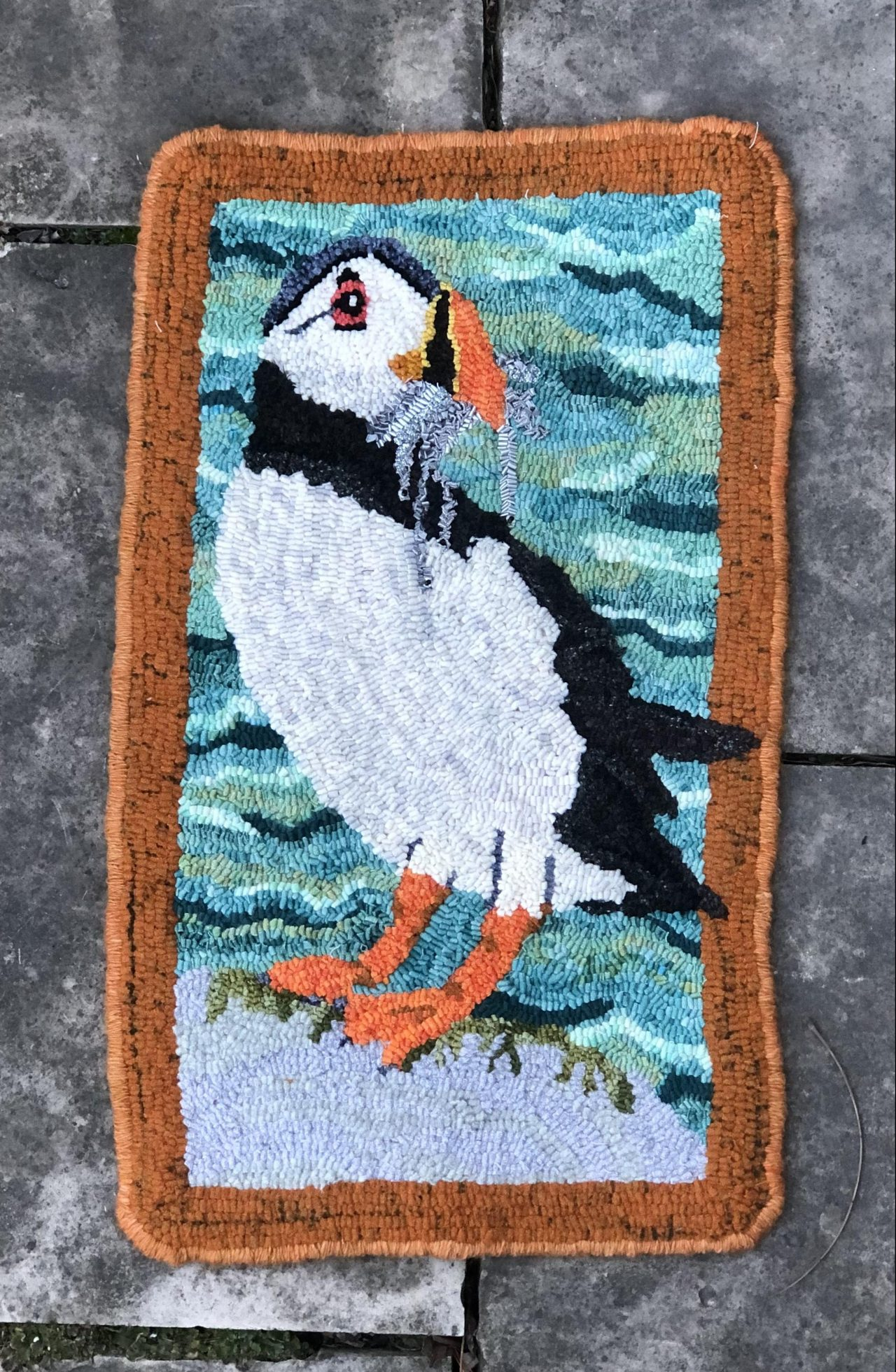 hooked rug art of a puffin with fish in its mouth by Yvonne Iten-Scott