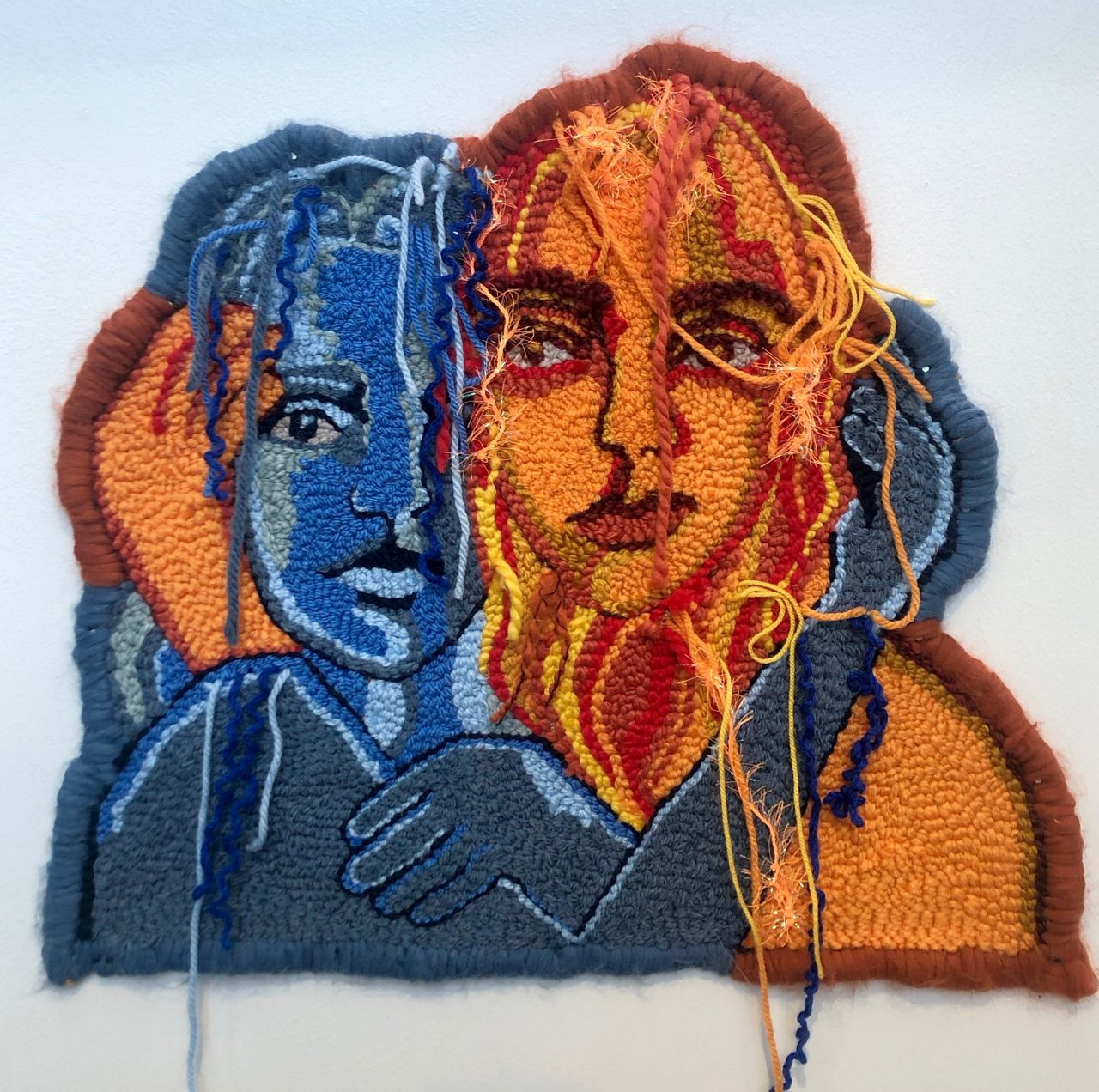 textile art by Selby Hurst Inglefield of 2 people, one in blues and the other in yellow and orange tones