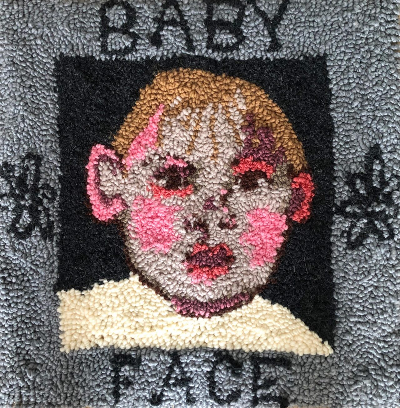 textile art of a small male childs face with words 'baby face' by Selby Hurst Inglefield