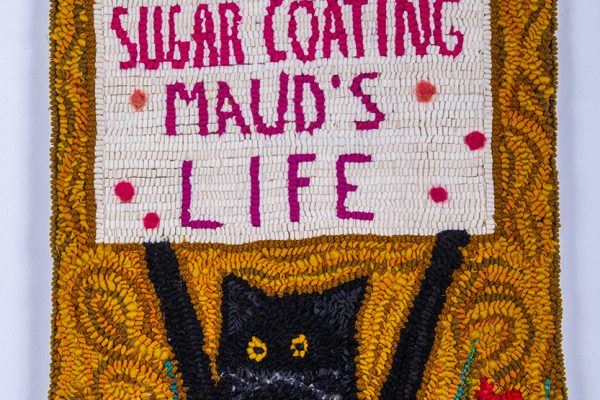 textile art featuring a cat holding a sign that says 'stop sugar coating Maud's life' by Laura Kenney