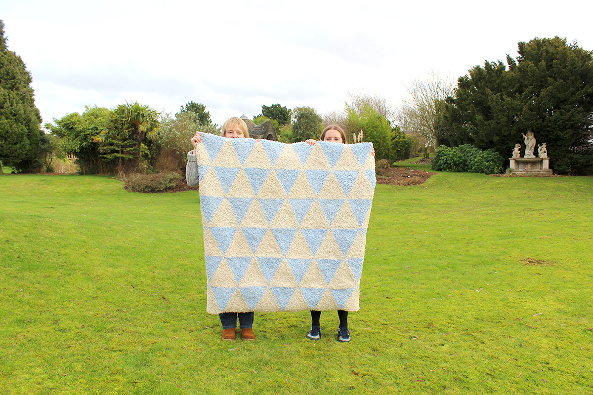 Women holding up large blue and cream triangle rag rug