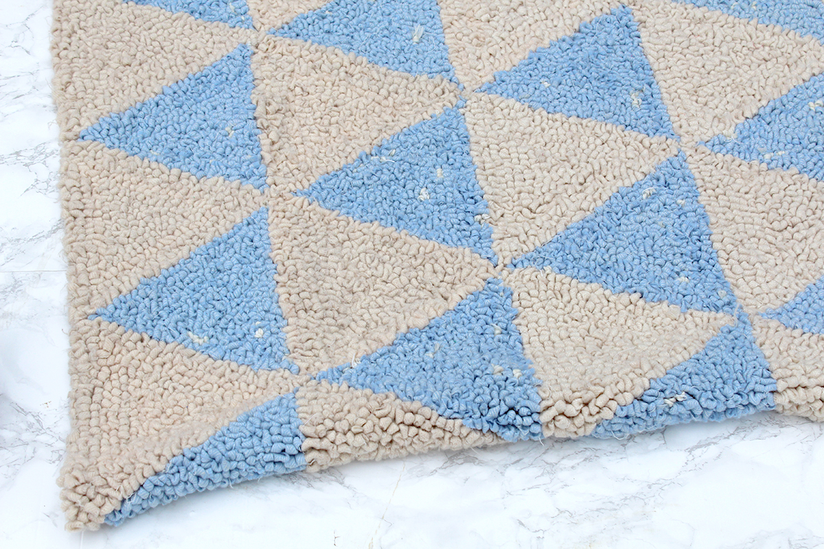 Baby blue and cream rug on marble floor