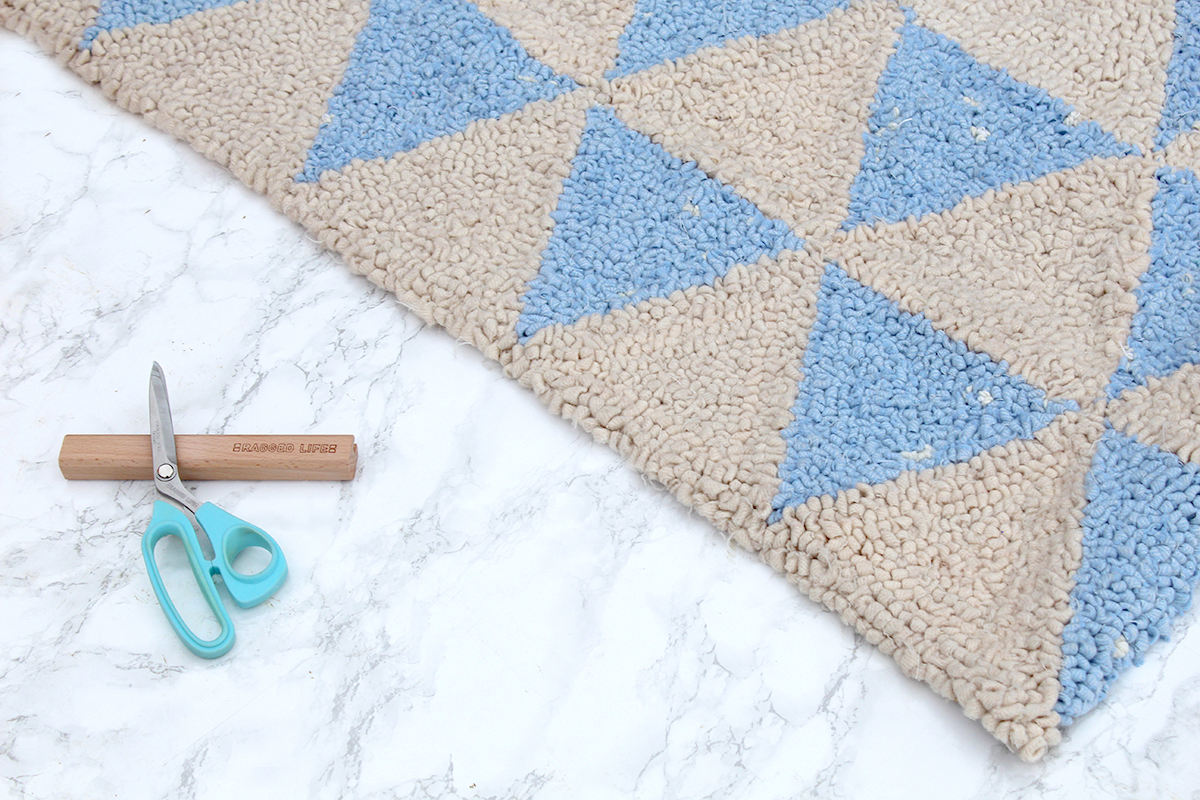 Hooked rag rug with scissors and gauge