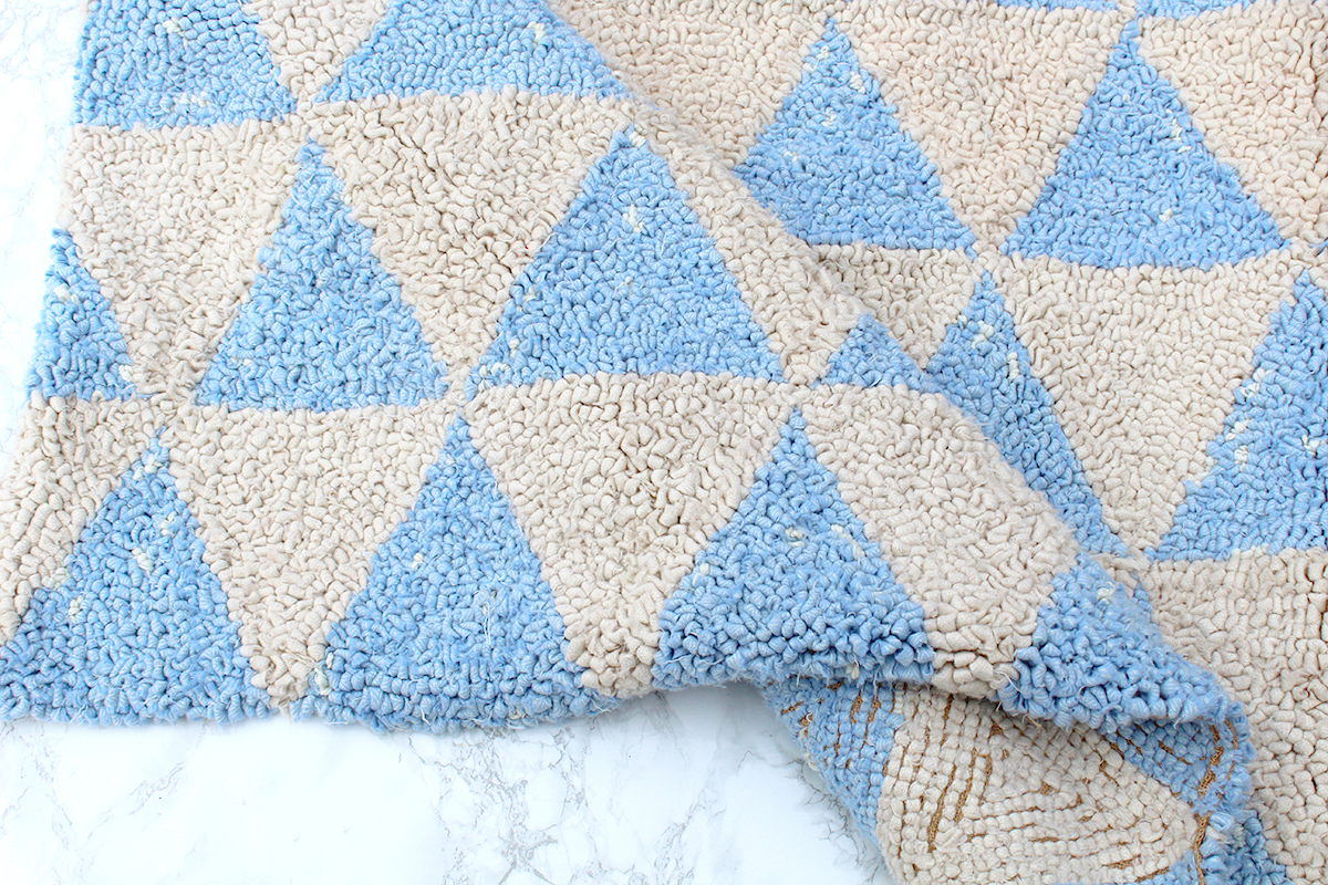 Folded over rag rug hooked with cream and blue fabric