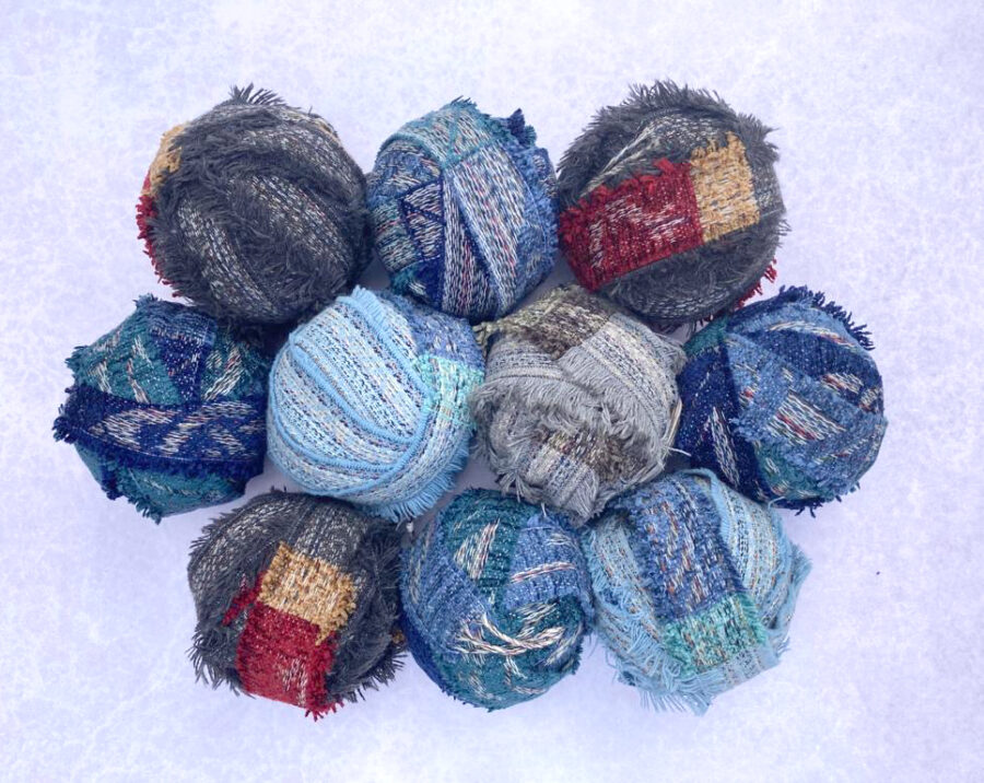 Group shot of blue and grey balls of chenille offcuts from the Yorkshire mills